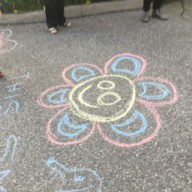 Kopernik essential worker support: flower with smile chalk drawing